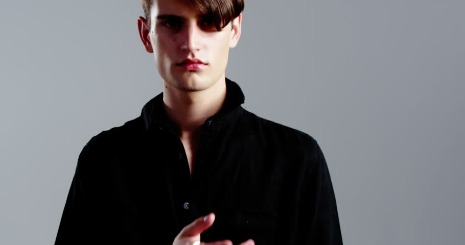Confident androgynous man posing against grey background