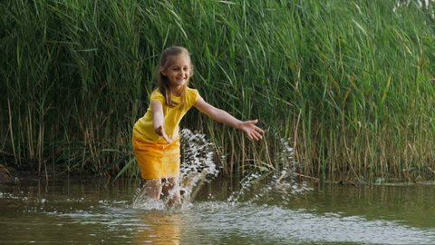 Little girl in yellow clothes stands in the water against the background of reeds and hands creates water splashes. Slow motion.