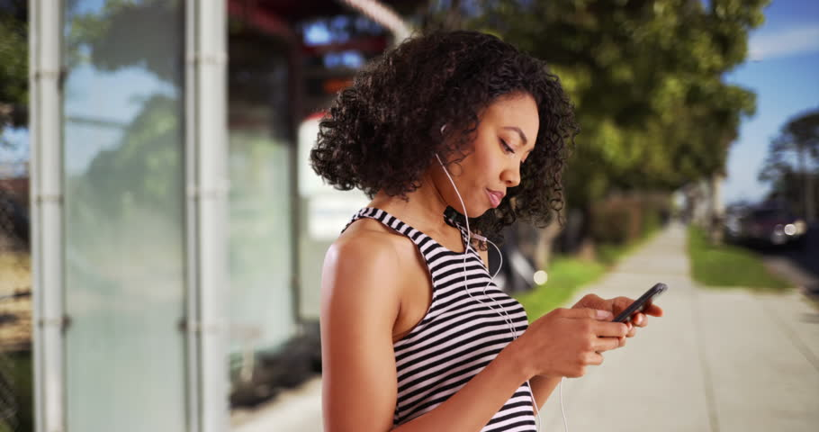 Profile of cute black female listening to cool song on cellphone, closing her eyes. Pretty African woman bobbing her head to music in outdoor setting on summer day. 4k   Shutterstock HD Video #29225212