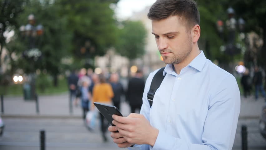 Young man holding tablet laptop device looking screen reading searching blurred city lights traffic people street outside dark hair handsome thoughtful quiet waiting technology tourist businessman | Shutterstock HD Video #29232814