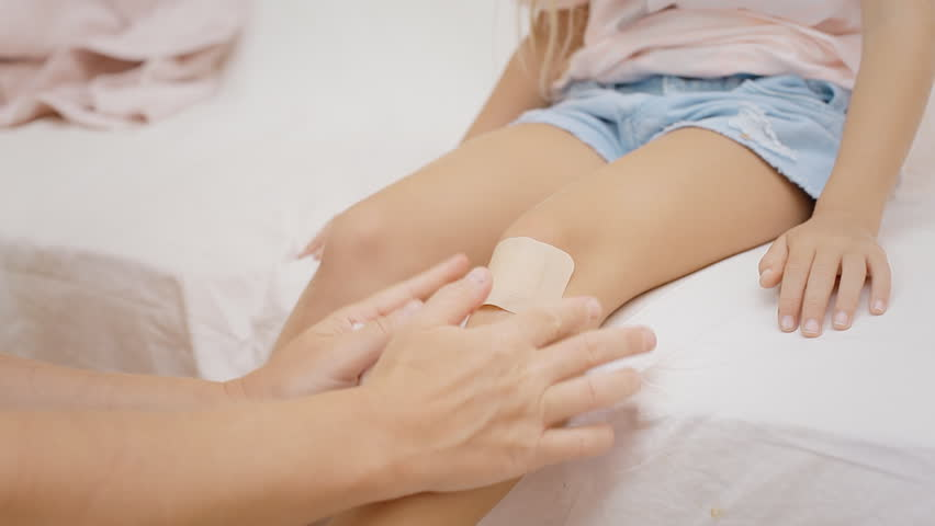 Cleaning a bleeding wound under the knee of a little girl and putting a band-aid over it.  | Shutterstock HD Video #29274580