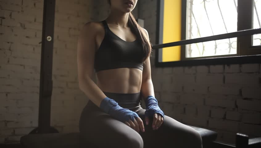 Well-built girl is sitting on the bowflex weight bench near the window in the boxing-room. Her hands are laying on her legs while her back is curved forward. She is breathing very deep and often
