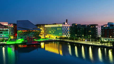 Dublin, Ireland. Aerial view of Grand Canal docks in Dublin, Ireland at sunrise. Empty streets and illuminated modern buildings, colorful clear sky. Time-lapse from night to day. Zoom in
