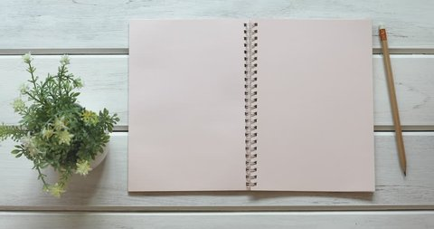 A male hand open diary paper 3 page  on the white wooden desk, top view and overhead shot use for blank template book mock up to add any text content, 4K Dci resolution
