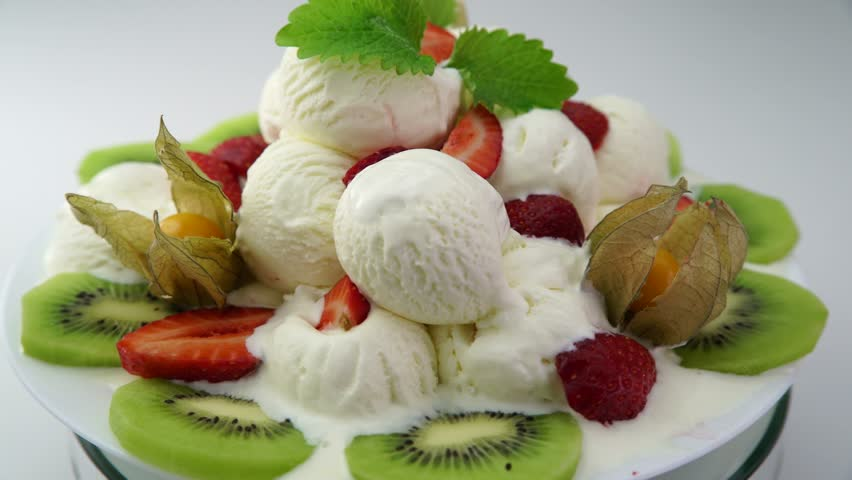 Delicious dessert with ice cream and fruits rotating on a plate over white background #29381500