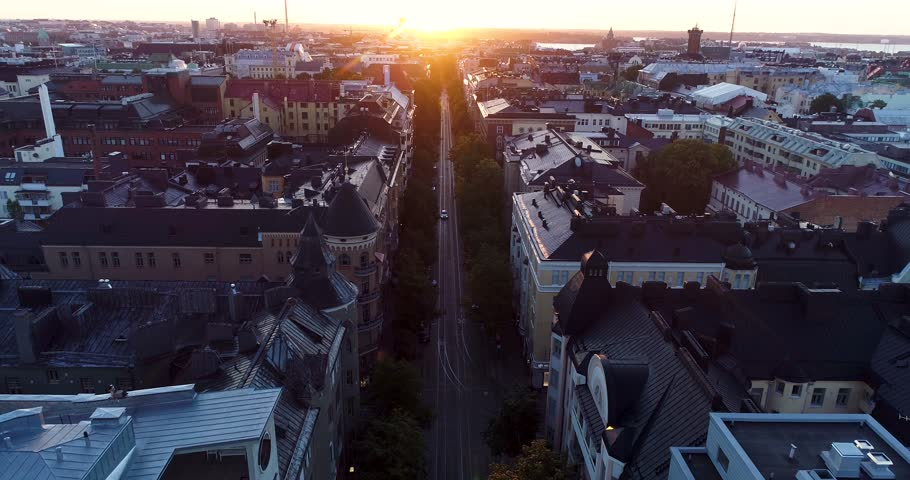 Aerial scenic view of Helsinki capital of Finland during sunrise. Drone flying backwards following a car above rooftops filming straight street line of Bulevardi ending at morning sun. Scandinavia