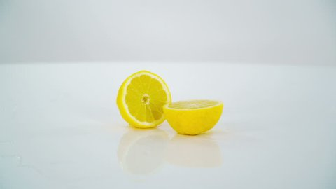The whole lemon falls down on a table and it splits into two halves. The water is on the table.