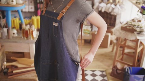 Midsection Of Small Business Owner Wearing Denim Apron In Store