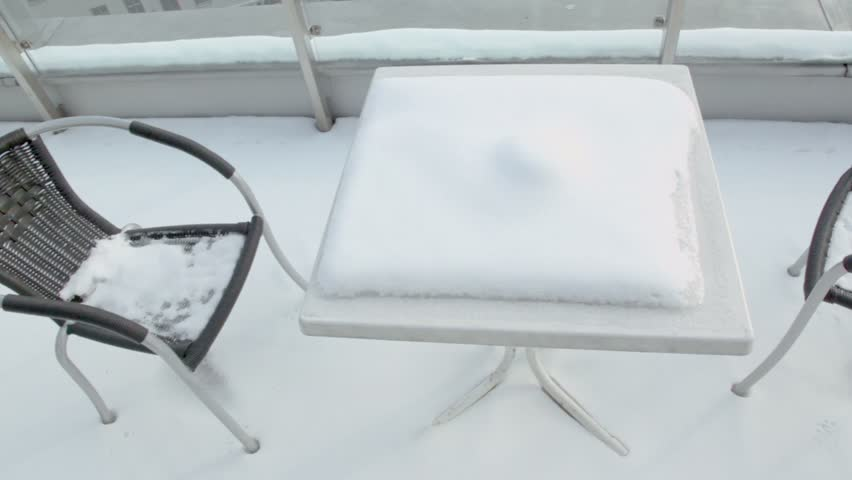 Chairs an table covered by snow at balcony near Europe square in Vienna, shown in motion