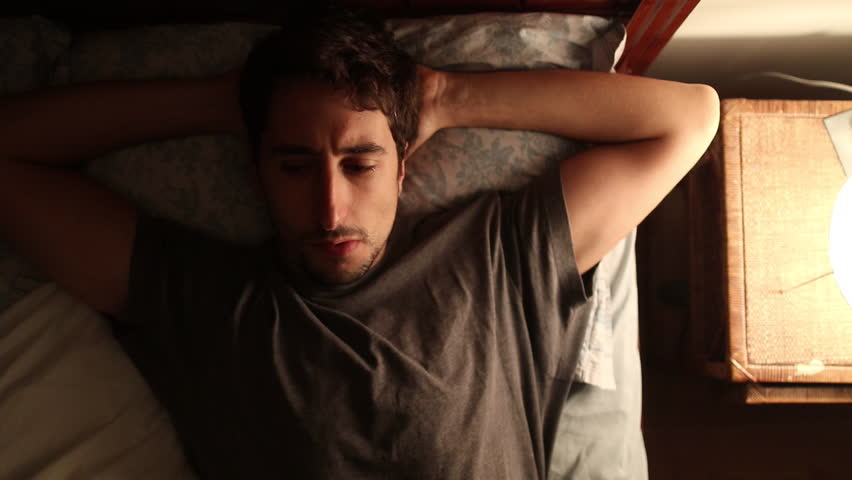 Thoughtful pensive young man lays down in bed, thinks about life for a moment, and then gets out in decision mode
