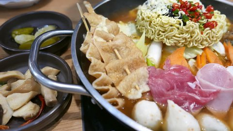 Korean Hot pot 'Budae Jjigae' or Army Stew is Korean fusion food incorporates American style with noodle, ham, sausages, canned baked beans, sliced cheese and Kimchi.