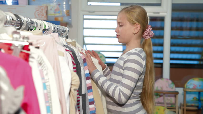 Little blond girl shopping for clothes in a clothing store, looking sweater. Side view | Shutterstock HD Video #2946934