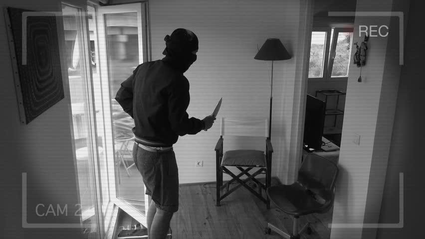 Home Security Camera Records A Home Burglary. Burglar with a gun breaks Into a house filmed on home security camera