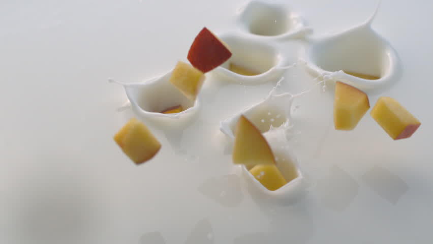 Pieces of Peach Falling into White Yogurt with Splashes