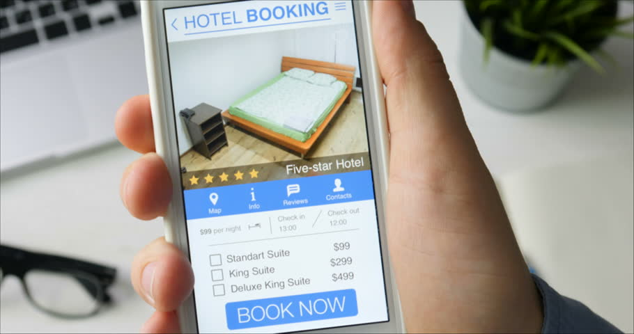 Man booking hotel suit using his smartphone and online booking mobile app sitting at his desk | Shutterstock HD Video #29520904