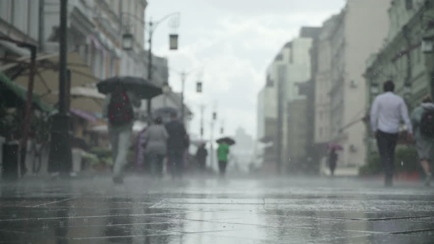 Background of heavy rain day on city street. Real time. People with umbrellas in the rain going to or from work. Blurred bokeh. Naturale backdrop