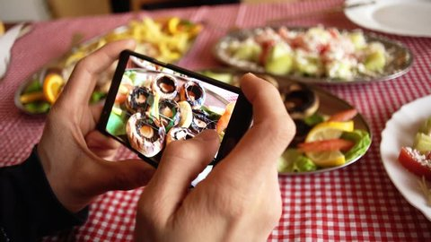 Hands of Caucasian male holding a smart phone and taking a photo of delicious food in a restaurant.