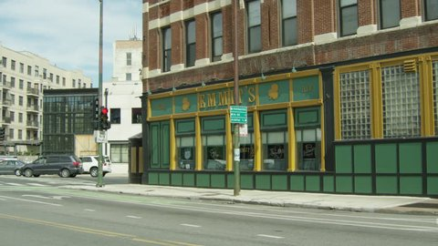 day hold corner Emmit's Irish Pub bar located bottom floor brick building, then pan up windows 4 story apartment building office building, raked right