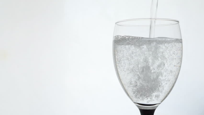 Cutout isolated closeup pouring clear aerated mineral water into transparent wineglass goblet glass on white background | Shutterstock HD Video #29555404