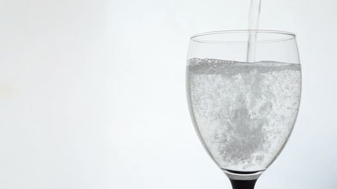 cutout isolated closeup pouring clear aerated mineral water into transparent wineglass goblet glass on white background