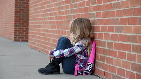 A young child is sad and alone outside a school brick wall for a lonely concept.