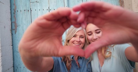 Mature mother and yound adult daughter making a heart shape with their hands and kissing