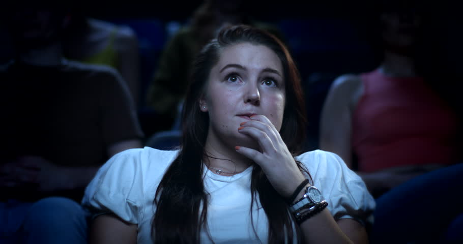 A young nervous woman at the cinema reacting to a scary movie | Shutterstock HD Video #29595364