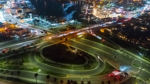 Aerial time lapse in motion or hyper lapse at night over a traffic circle onramp and up street showing streaks of car lights, city buildings and parking lots, showing the fast paced city lifestyle.