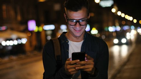 Close up shot of attractive man in the stylish glasses using smart phone in the street at the evening time on the light background.