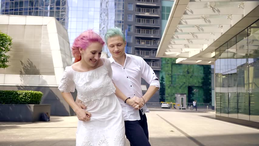 cheerful young guys go out and fool around on the street. brightly coloured hair pink and blue
