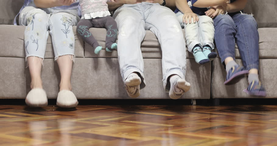 A cheerful family is sitting on the couch and playing with their feet. 4K footage.