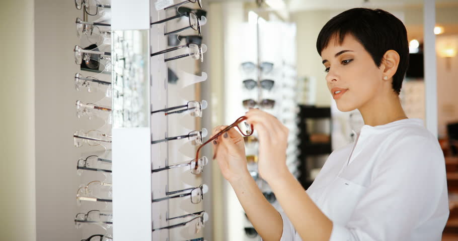 health care, eyesight and vision concept - happy woman choosing glasses at optics store #29634694