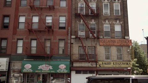 May 2016. Polish businesses on Manhattan Ave, Greenpoint, Brooklyn, New York. Polish neighborhood. Old, red brick apartment buildings. Fire steps. Signboards. Storefronts. Hand held camera work.