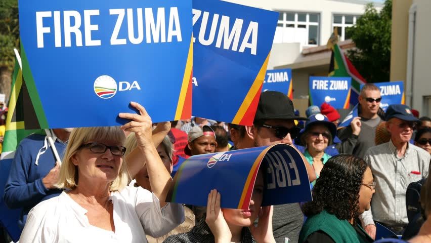 """CAPE TOWN SOUTH AFRICA, 8 AUGUST 2017, day of Zuma no confidence vote in parliament, a white woman holding """"Fire Zuma DA"""" placard another holding one over her head, others in background out of focus"""