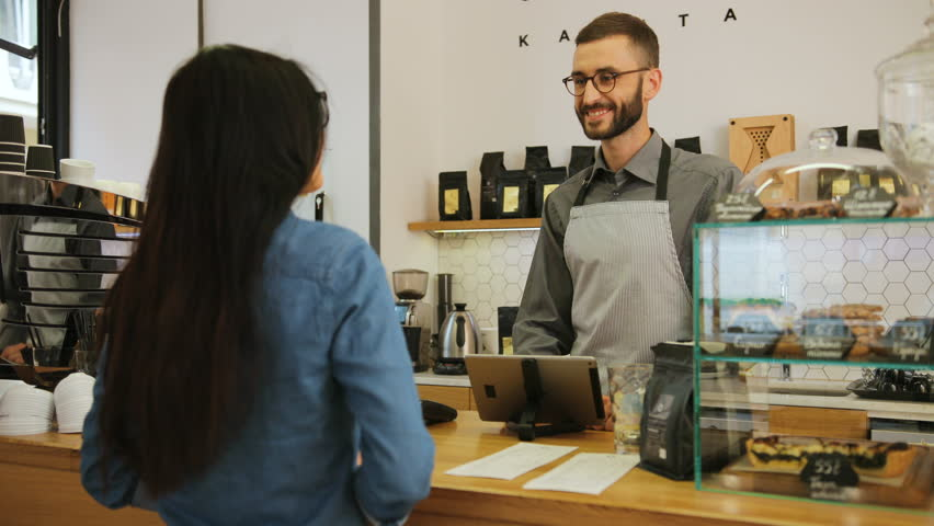 Portrait of young caucasian woman buying coffee in a stylishcoffee shop from a male barista and paying by credit card.