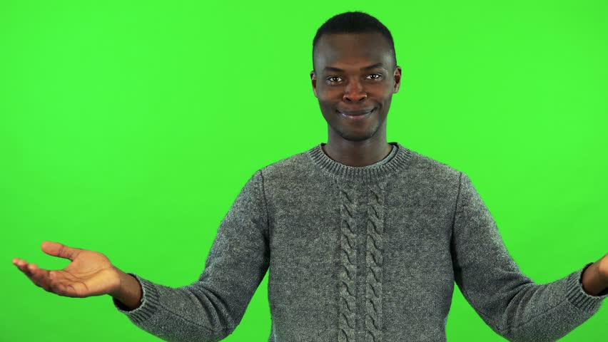 A young black man jumps up into the shot and smiles at the camera - green screen studio | Shutterstock HD Video #29687374