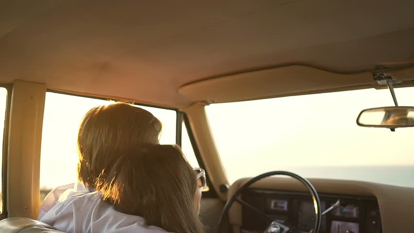Back view of hugging couple siting in retro car and holding their hands together | Shutterstock HD Video #29695654