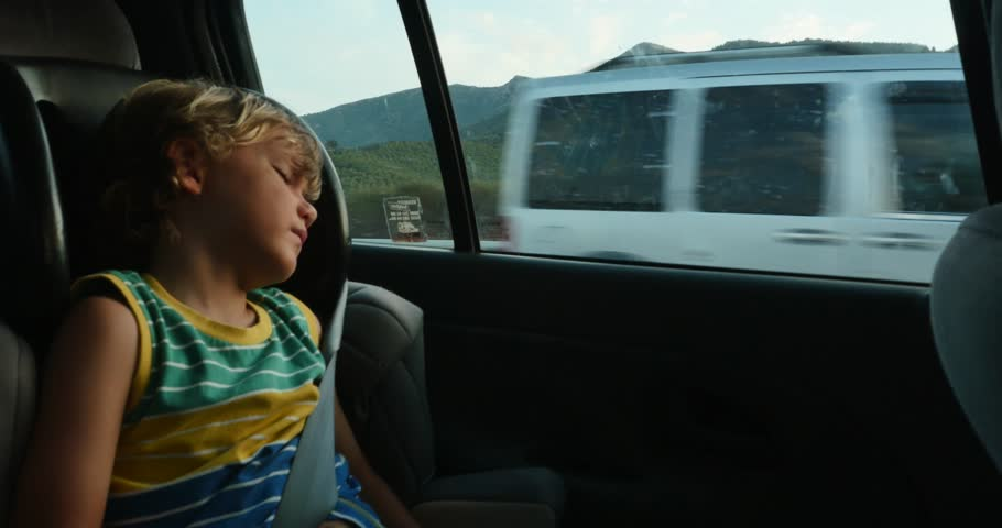 child boy sleeping in car journey