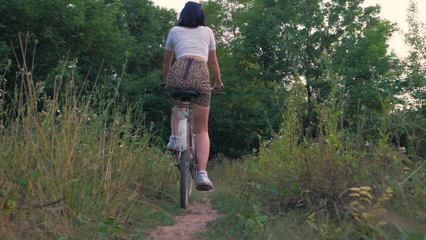 Young beautiful woman in short skirt riding vintage old bicycle in the forest at summer. Slow motion.