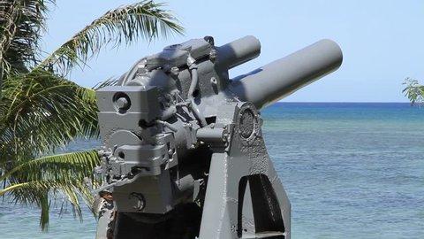 Steady shot footage, back view of a japanese 20cm coastal defense gun at  gun beach, guam facing the ocean