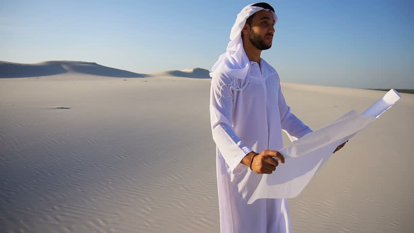 Handsome young Arabian UAE Sheikh male Arab businessman looks at future construction project plan and mentally presents and transports to terrain, looks around and stands in middle of wide desert with