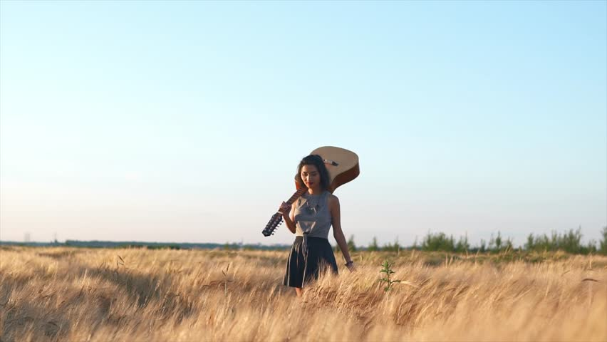 Young woman walking with a guitar at wheat field