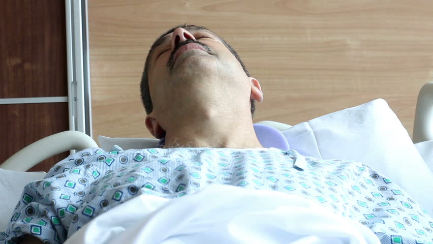 Unconscious man in bed in a modern hospital