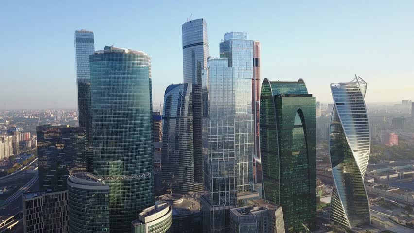4K aerial view drone video of Moscow City area, International business centre, Moscow River with bridge, skyscrapers and boats along the river in Russia on calm quiet sunny summer August morning