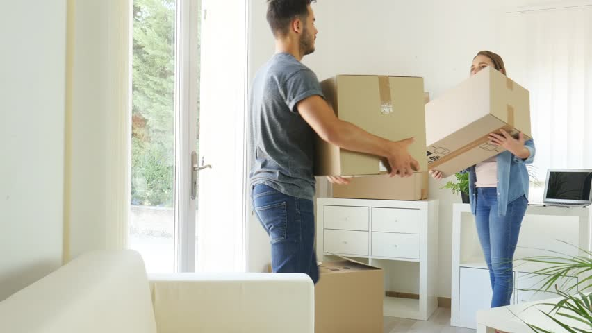 happy young couple student roommate packing boxes and moving furniture during move into new home flat apartment