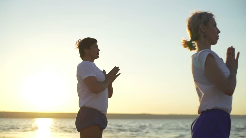 53cbf6f28d Group of people practice yoga namaste pose seaside sunrise rapid slow motion