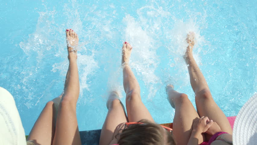 SLOW MOTION CLOSE UP: Three unrecognizable cheerful girls sitting on pool edge, splashing water with their feet on hot sunny day. Three playful young women on summer vacation splashing water with legs