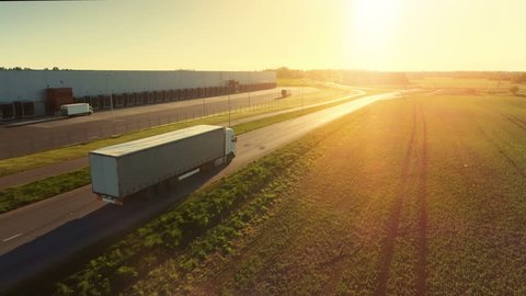 Aerial Follow Shot of White Semi Truck with Cargo Trailer Attached Moving Through Industrial Warehouse, Rural Area. Sun Shines and the Sky Are Blue. Shot on Phantom 4K UHD Camera.