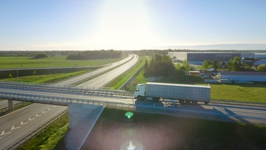 Shot on RED EPIC-W 8K Helium Cinema Camera.Aerial View of White Semi Truck with Cargo Trailer Passing Highway Overpass/ Bridge. Eighteen Wheeler is New, Loading Warehouses are Seen in the Background.