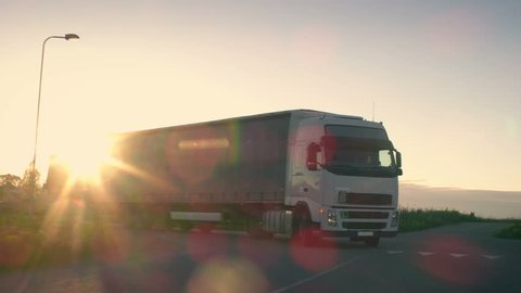 Semi Truck with Cargo Trailer Turns and Drives Through the Highway. Truck is White and New. Sun Shines in the Background. Shot on RED EPIC-W 8K Helium Cinema Camera.